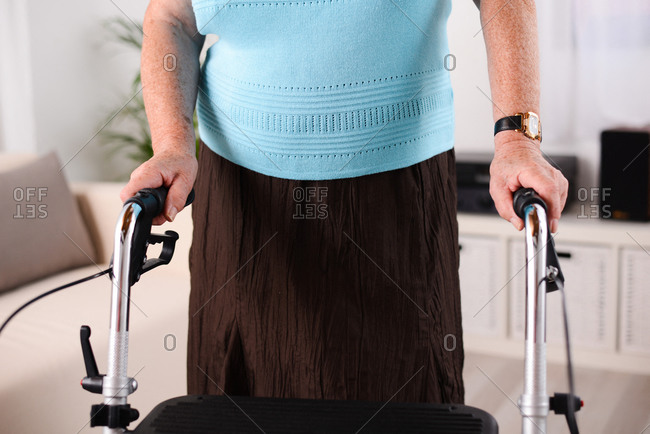 close up hands shot of elderly senior woman using walker rehab indoor