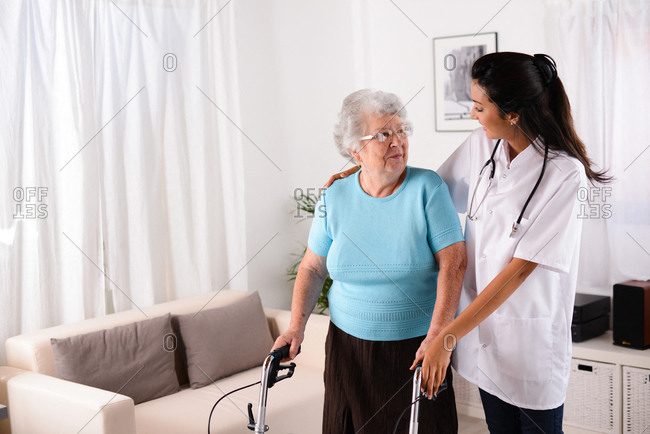 cheerful young rehab nurse helping elderly senior woman using a walker