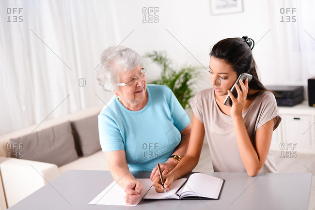 cheerful young woman helping an old senior person doing paperwork and telephone call