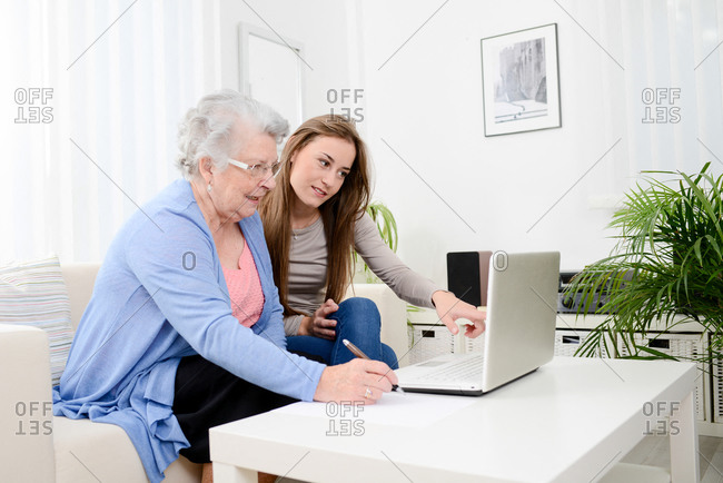 Cheerful young woman helping a senior woman at home with laptop computer