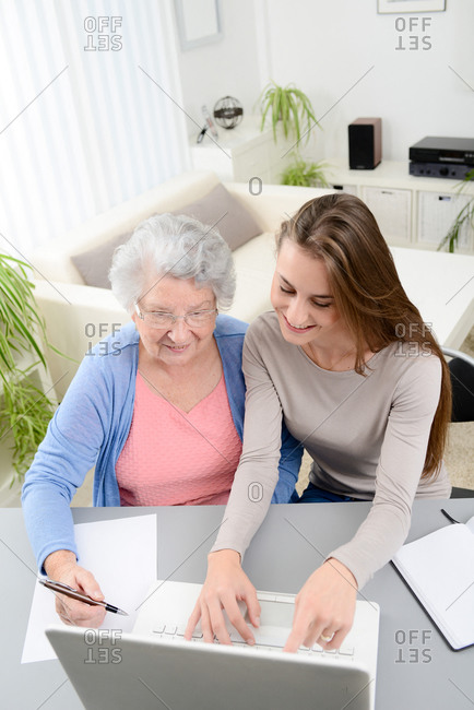 Young woman helping old senior woman doing paperwork and administrative procedures with laptop computer at home