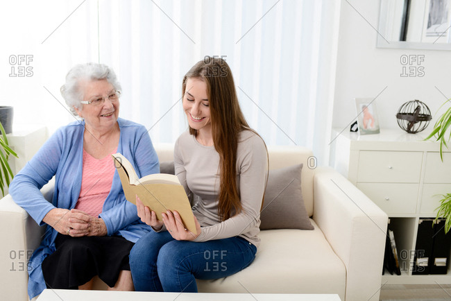 Cheerful young woman reading a book for an old senior woman at home