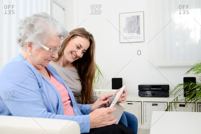 Cheerful young girl sharing time with old senior woman and teaching internet with computer tablet