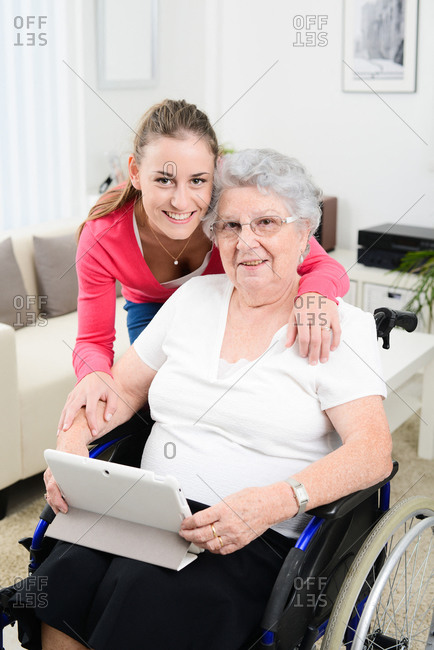Cheerful young girl playing on internet with tablet computer and sharing time with old senior woman on wheelchair
