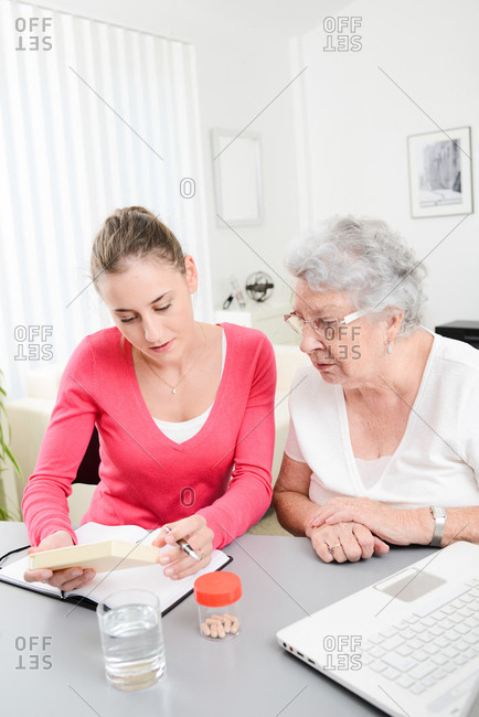 Cheerful young woman helping elderly woman with pills medical prescription