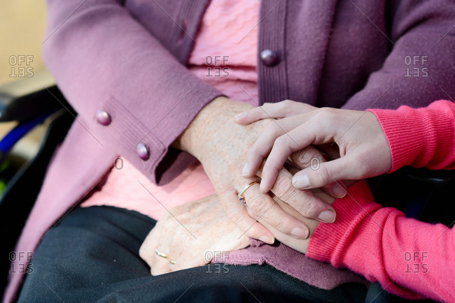 Detail of young woman's hands holding with tenderness an old senior woman's hands.