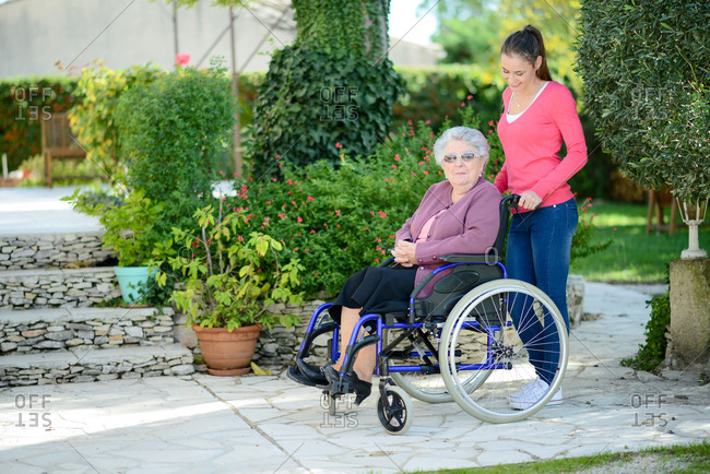 Cheerful young woman in a retirement house garden with a elderly senior woman.