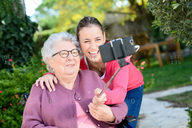 Cheerful young woman making a selfie with a elderly senior woman in a retirement house garden.