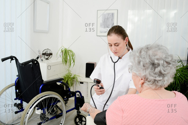 Elderly senior woman with young doctor having medical care at home.