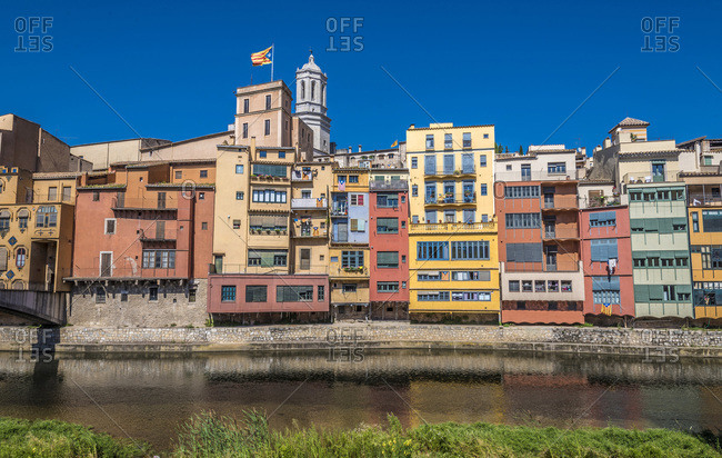 Spain Catalonia, Girona, Onyar river, colored facades of the old town, flag and bell tower of the Girona cathedral