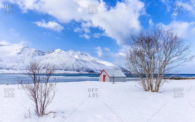 Norway, Tromso County, Senja Island, Ballesvika Fjord with snow