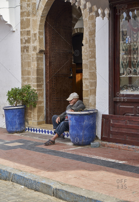 Essaouira, Morocco - November 08 2017: Lonely local man sitting on a street in the Medina of Essaouira