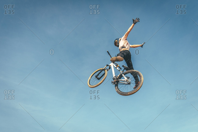 Carefree man performing stunt with bicycle against blue sky during sunset