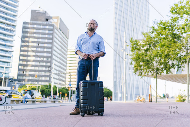 Businessman with wheeled luggage standing on footpath in city