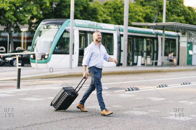 Businessman with wheeled luggage crossing street in city