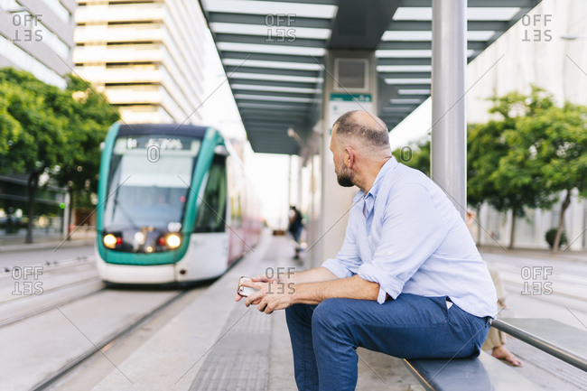 Businessman looking at tram while sitting on bench at station in city