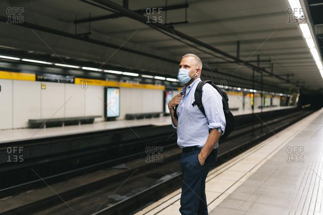 Businessman wearing face mask while standing at subway platform