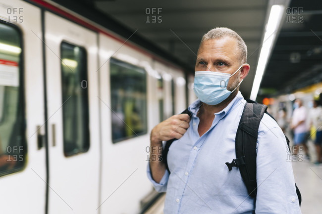 Businessman in protective face mask at subway station