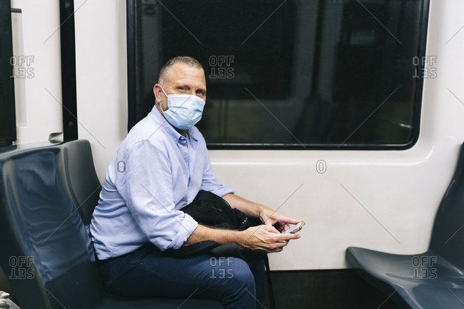 Businessman wearing face mask while traveling in subway train during COVID-19
