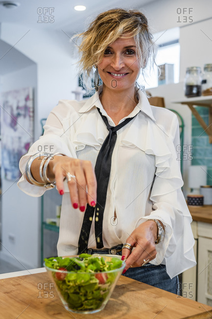Smiling female chef sprinkling spices on salad in cooking school
