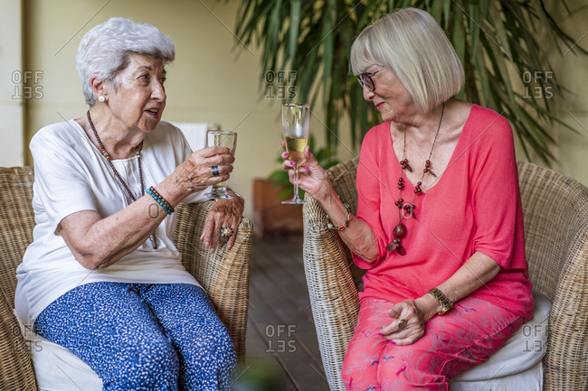 Senior female friends toasting champagne flutes while sitting on chairs at patio