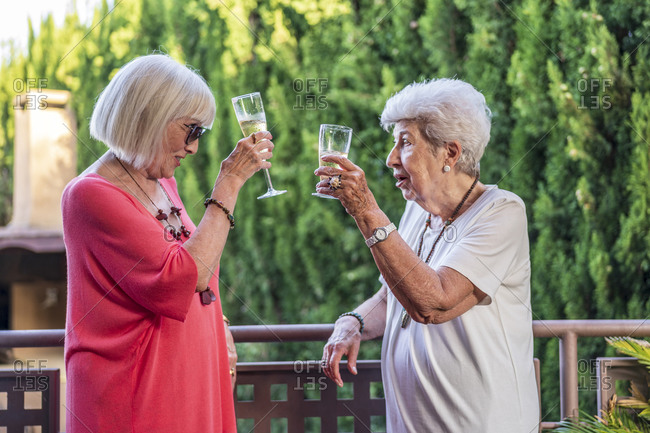 Senior female friends toasting champagne flutes while standing by railing in balcony