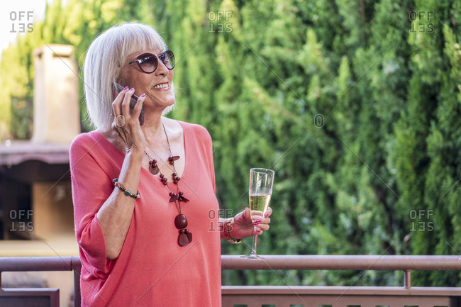 Senior woman holding champagne flute talking over mobile phone while standing in balcony