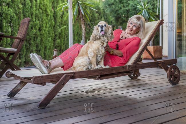 Stylish senior woman with dog relaxing on lounge chair in patio