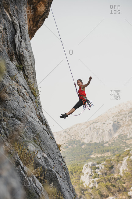 Carefree female rock climber rappelling on rocky mountain