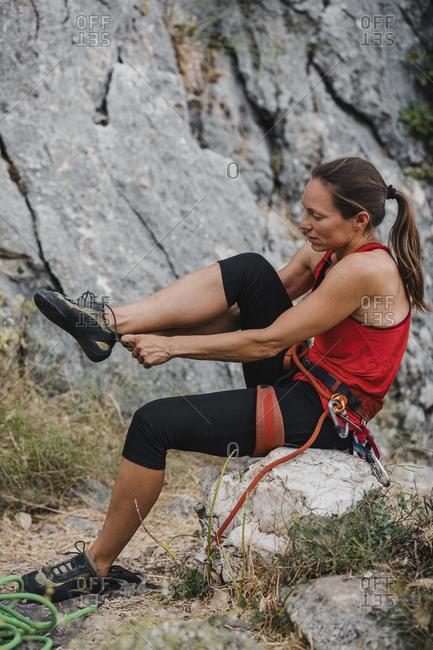 Female climber wearing shoe while sitting on rock
