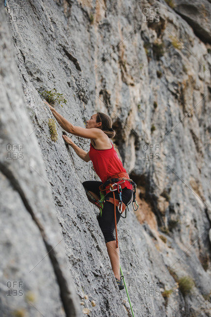Determined female climber climbing rocky mountain