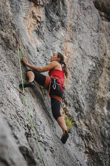 Confident woman climbing rocky mountain using rope