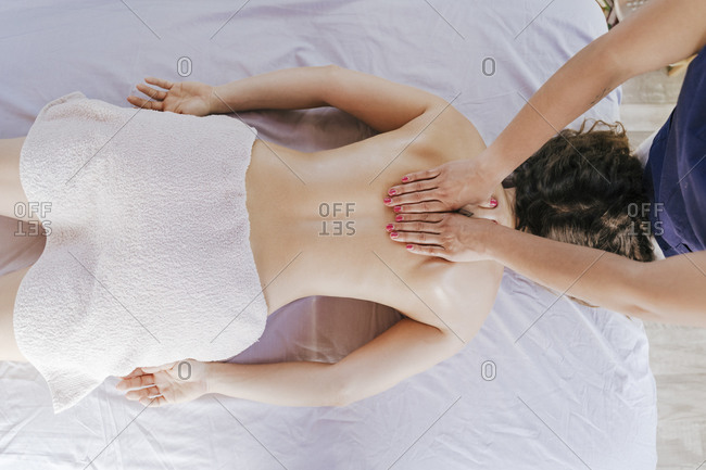 Therapist giving back massage to female customer lying on table in spa