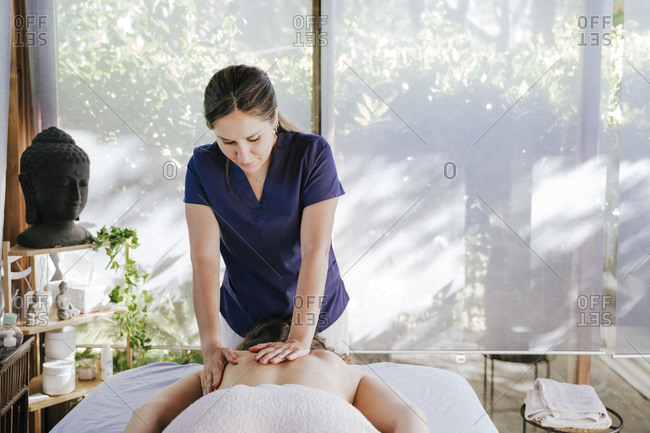 Mid adult woman giving back massage to female customer lying on table in spa
