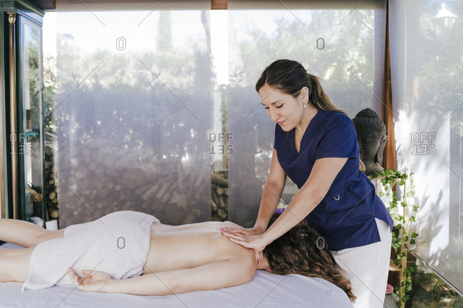 Smiling female therapist giving back massage to woman lying on table in spa