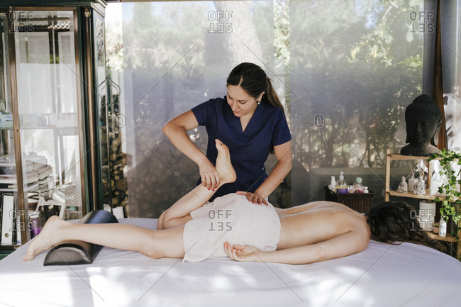 Female therapist giving leg massage to customer relaxing on table in spa