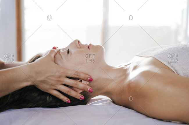 Close-up of female therapist giving head massage to customer resting on table in spa