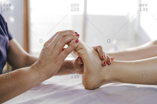 Close-up of therapist giving foot massage to female customer on table in health spa