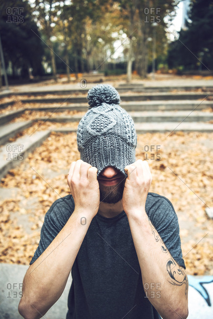 Young man covering face with knit hat while standing in park during autumn
