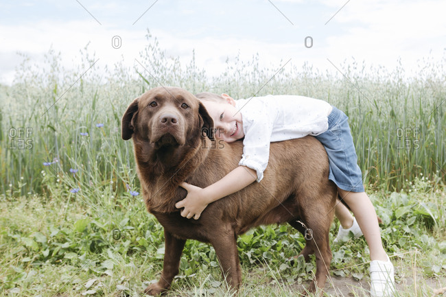 Smiling boy embracing Chocolate Labrador while standing against plants