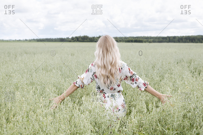 Young woman with blond hair standing amidst oats field against cloudy sky