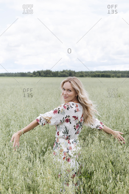 Beautiful woman with blond hair standing amidst oats field against cloudy sky