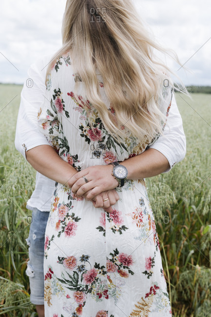 Loving husband embracing young woman while standing amidst oats field