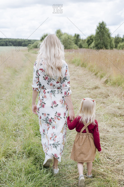 Mother and daughter with blond hair walking on grassy land against sky
