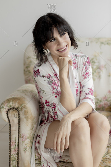 Smiling beautiful woman in nightwear looking away while sitting on armchair