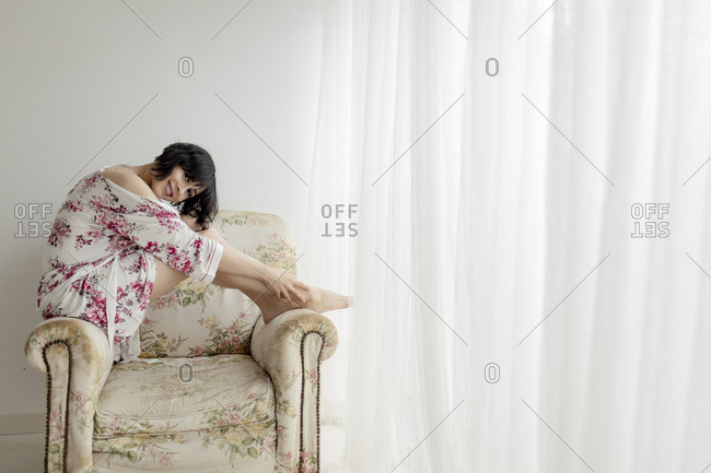 Woman in nightwear sitting on armchair at home