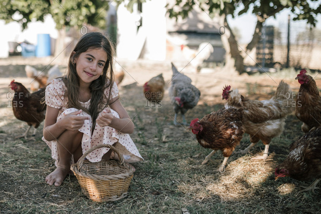 Girl with basket sitting in chicken farm