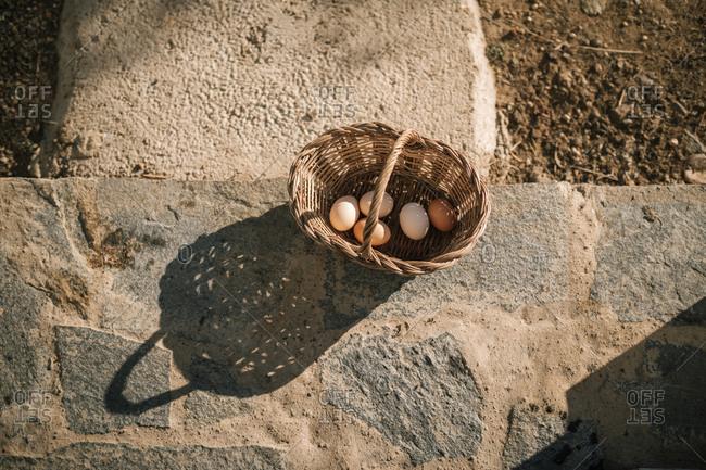 Eggs in wicker basket over stone floor