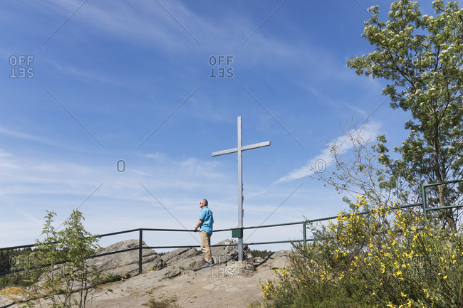 Germany- North Rhine-Westphalia- Monschau- Man admiring views by cross standing on summit of Ehrensteinley