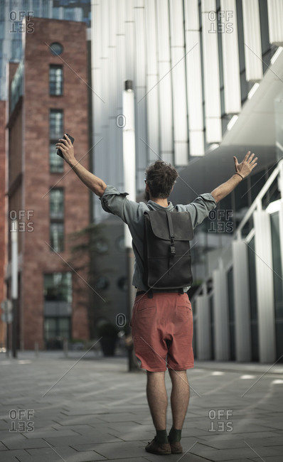 Man standing with arms outstretched on street in city